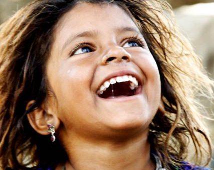 A criança sorri com tão pouco